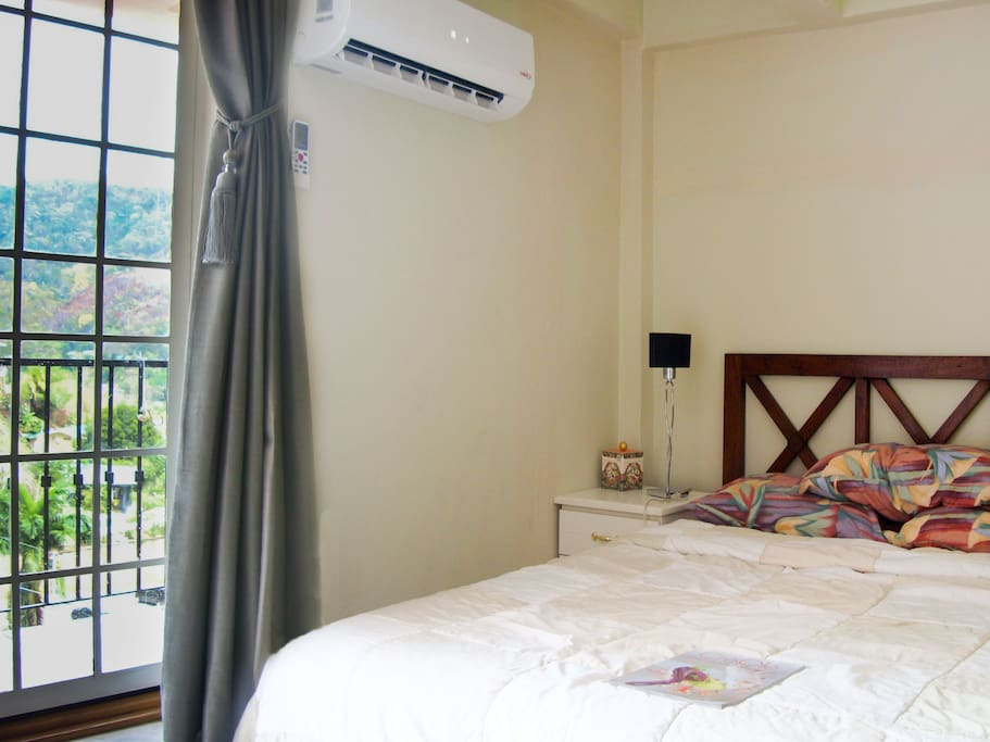Queen-sized bed indicating a/c and Juliette balcony