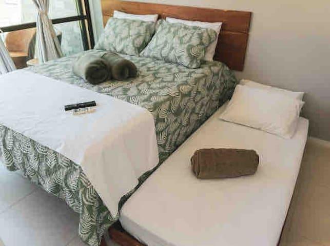Suíte com cama queen mais cama de solteiro com varanda e vista para piscina.