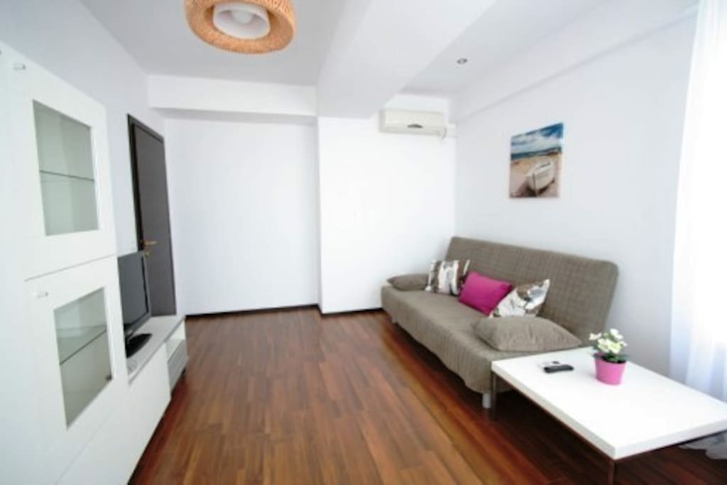 The living room is open space and it is equipped with air conditioner, LCD TV, table and sofa for 2 tourists.