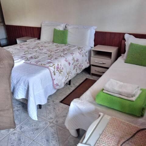 Quarto tripo com tv lareira e frigobar cama de casal e uma cama de solteiro e banheiro
