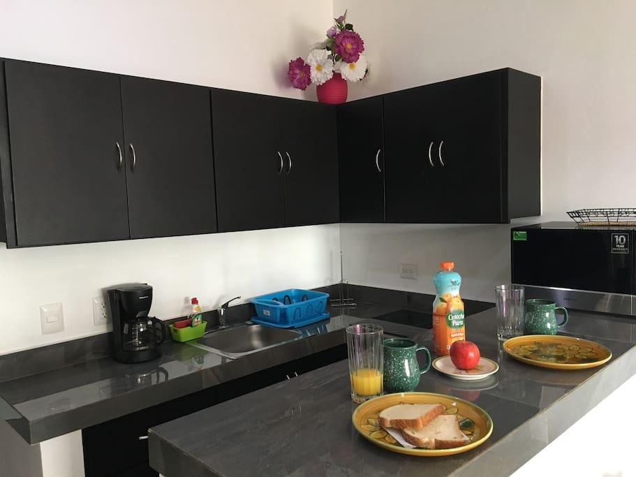 Cocina equipada con sartenes, platos, vasos y cubiertos. Cuenta con refrigerador, estufa de inducción, microondas, cafetera, tostadora y licuadora.