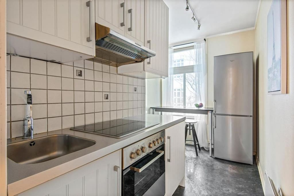 Modern kitchen with dishwasher, full size refrigerator and a breakfast table for two. Enjoy your coffee overlooking the backyard.