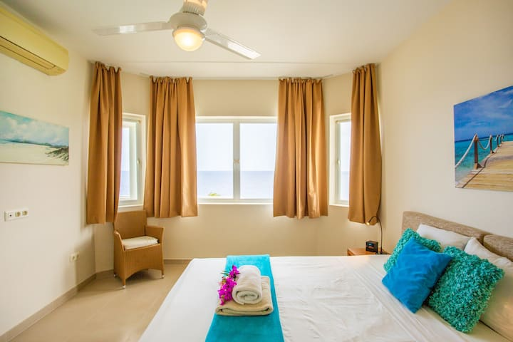 The 2nd bedroom has a king size bed, sea view, air conditioning, a private bathroom, ceiling ventilator and screens for the windows.