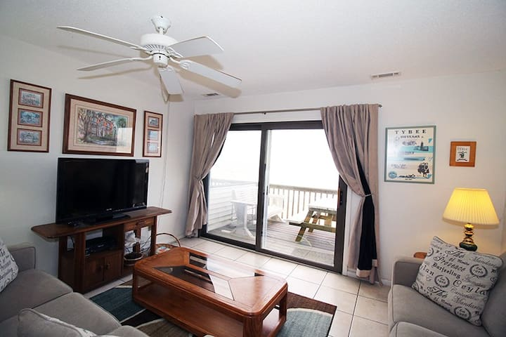 Comfortable living room with a flat screen TV, queen sized sofa sleeper, balcony access, and incredible ocean views