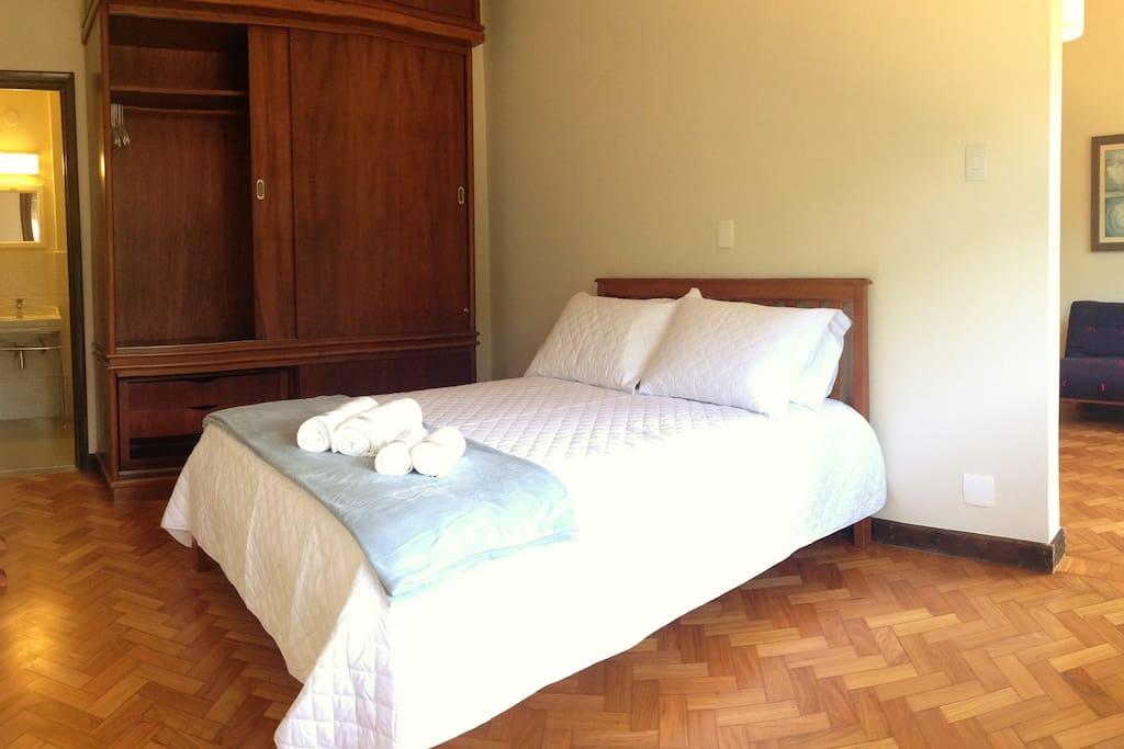 Quarto com cama de casal, armário e ar refrigerado