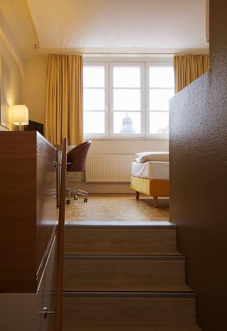 Eine kleine Treppe führt im Eingangsbereich in den Wohnbereich, links davon der Kleiderschrank, rechts davon das Bad.