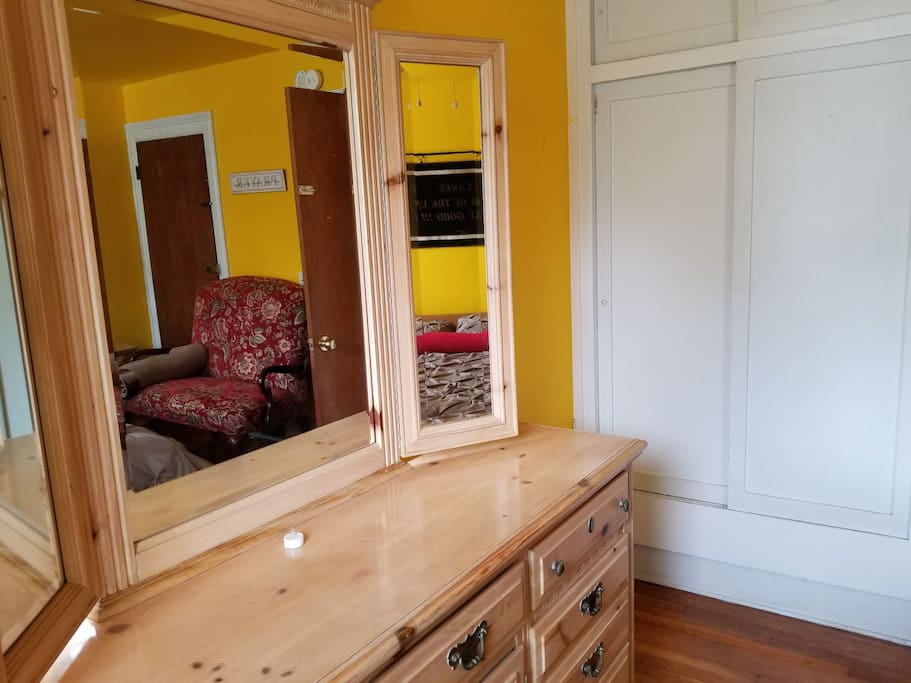 Bedroom has dresser with mirrors