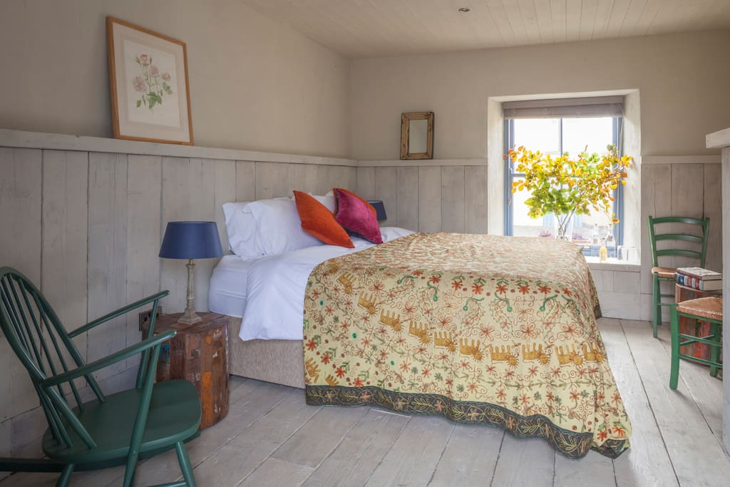 The Ploughman's Room, with bright, south facing window, reclaimed panelling and superking size bed. Each room is ensuite with crisp white linen, smart bathroom, local handmade bath products, a superking sized bed and its own private entrance onto the sunny courtyard - through a cute stable door.
