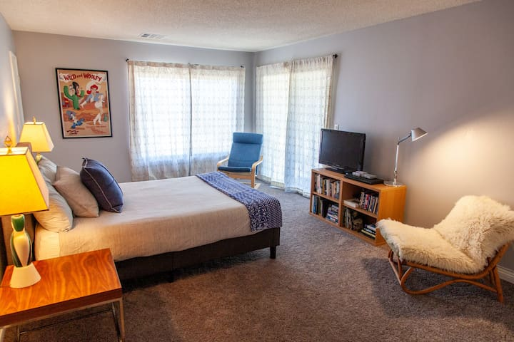 Large second bedroom has an attached half-bath, closet, TV with a fully loaded Roku, DVD player, and SNES and Playstation Classic game consoles.