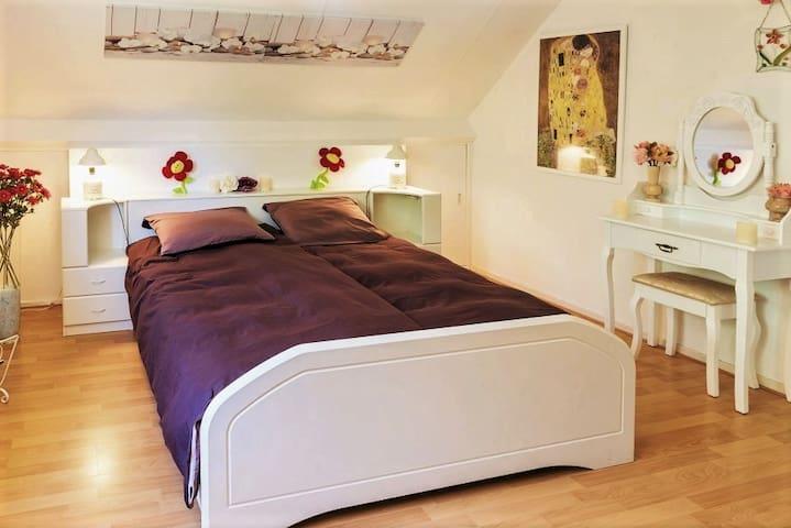 Ouderslaapkamer met romantisch 2-persoonsbed en kaptafel.