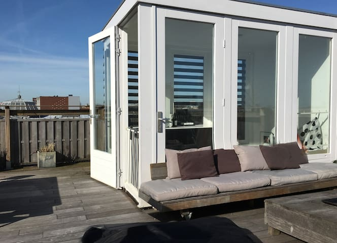 The roof terrace with lounge seats and views all over Amsterdam; from the business district ZuidAs, the Vondelpark, the Central Bank building to Schiphol airport's control tower.