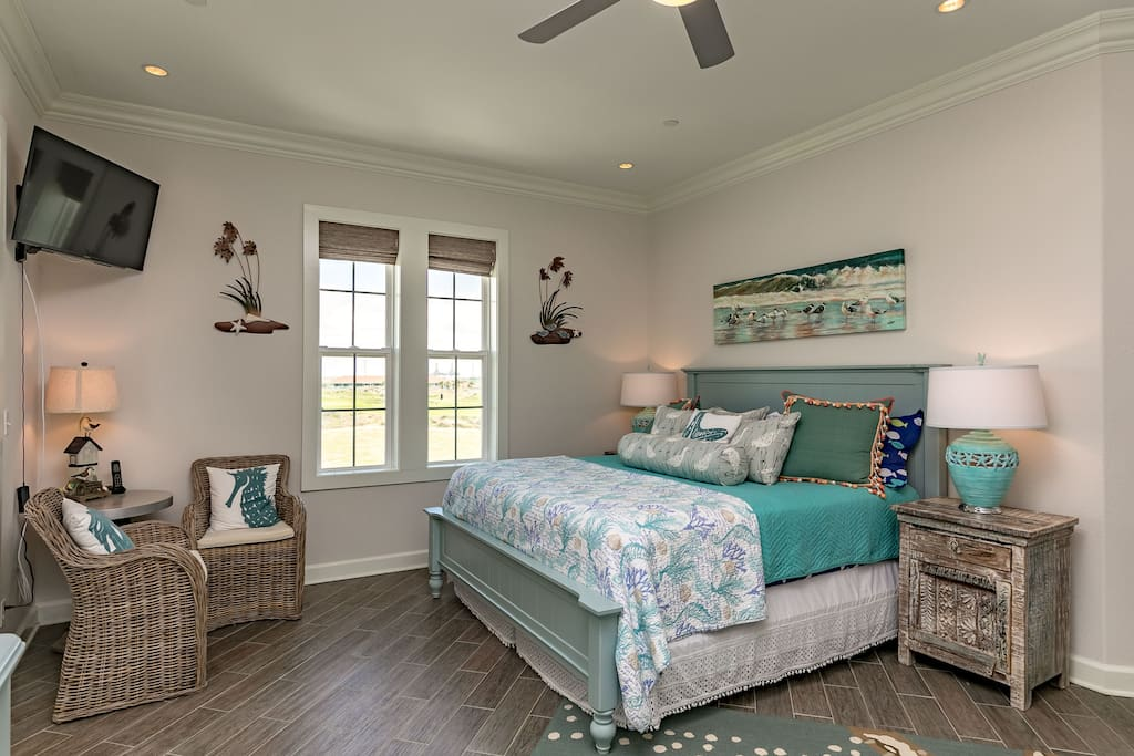 A king bed, beach-themed decor, wicker chairs, and floors on the diagonal characterize this room.