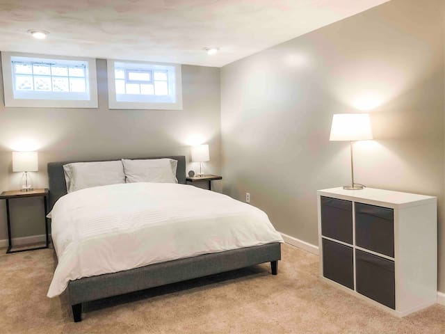 Queen bedroom w/ half bath located in carpeted basement. 100% cotton bedding. Alarm clock with USB port.