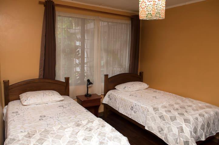 HABITACIÓN PECHOAMARILLO. Tiene dos camas individuales de madera semi preciosa, amplio closet, mesa de noche, lámpara, escritorio, silla para trabajo o estudio.