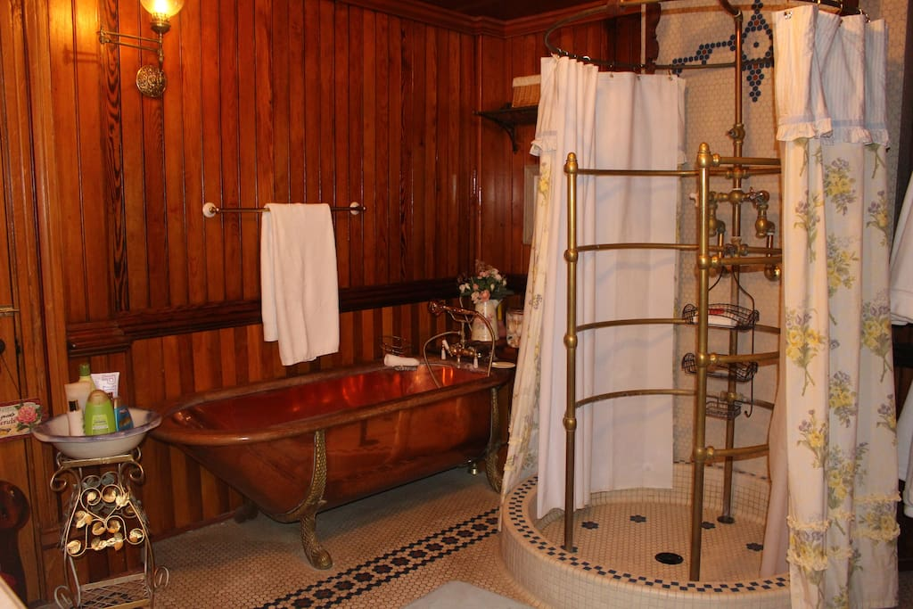 Private master bath features a copper claw foot bathtub and an antique brass shower surround just like the one in the Biltmore Mansion .