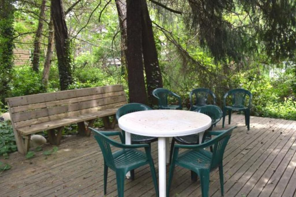 Semi-private back deck with a built in bench seat, patio table and chairs and a gas BBQ