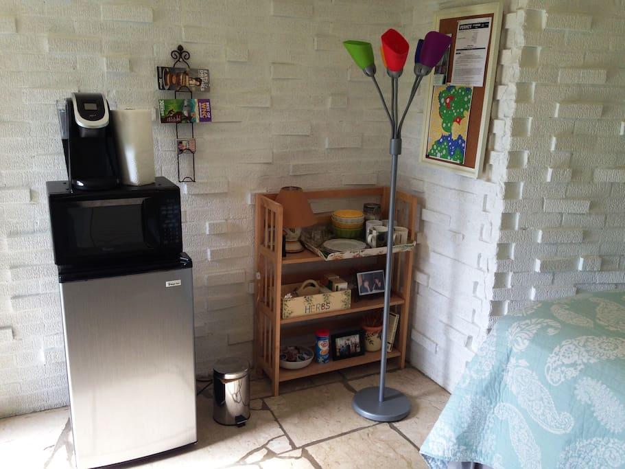 The room has a mini fridge, a microwave, and a Keurig 2.0 coffee maker.