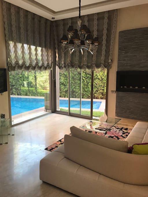 Salon avec cheminée, vu sur piscine