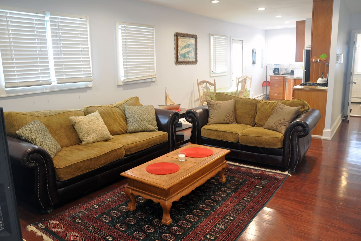 spacious yet cozy living room area w/ couches, tables, tv, lots of space & light