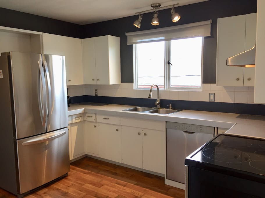 Large kitchen with stainless steel appliances filled with all the amenities you need to stay in and cook