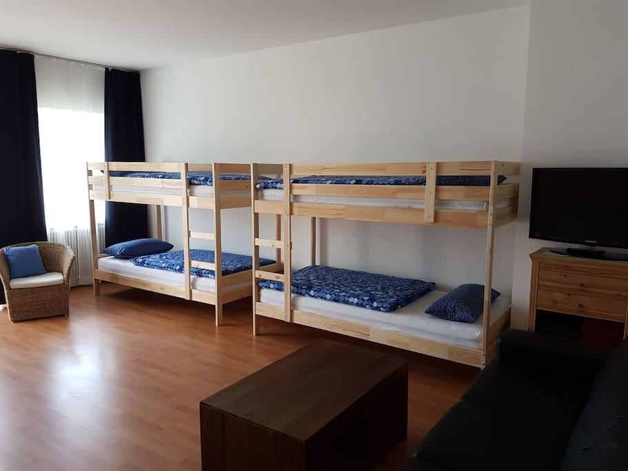 Guest room with 4 bunk beds, couch, couch table and TV