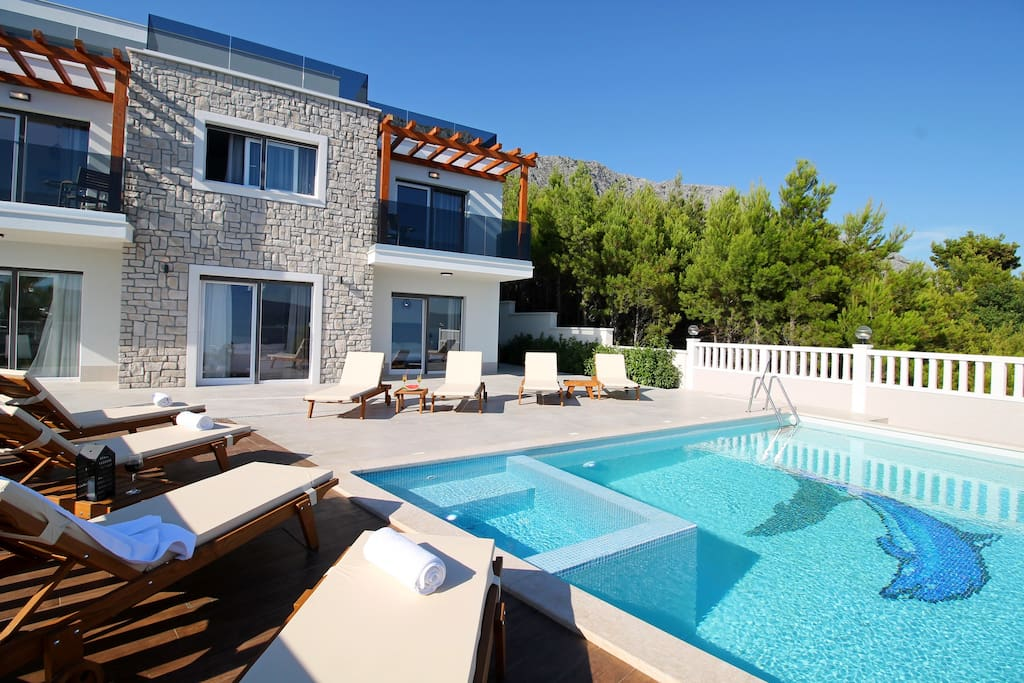 Heated pool with whirlpool and 8 lounge chairs on sun deck area