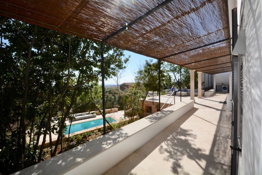 The house with covered and open terraces overlooks the pool area, gardens and the city of Palma.