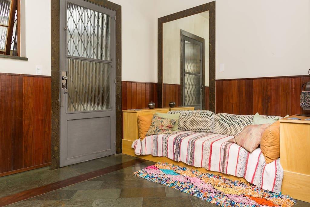 Sala de estar sofá, porta de entrada fechada, janela para manter a ventilação.