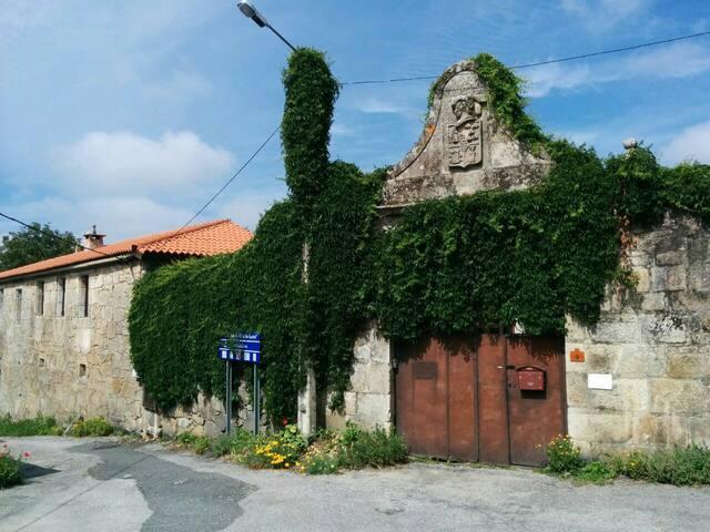 La fachada del Pazo con la entrada al patio, con escudo arriba.