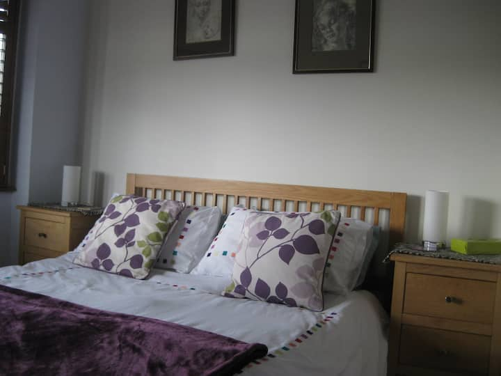 Spacious double bedroom with king size bed .