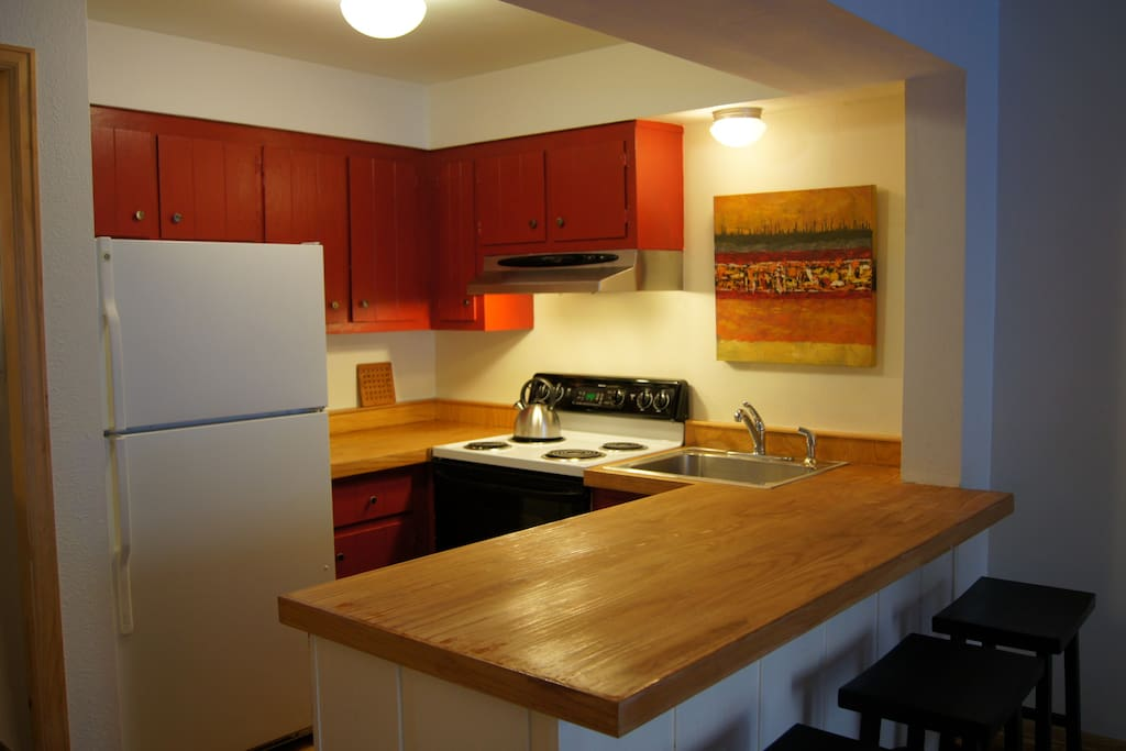 Kitchen with wood countertops and full-size stove, dishwasher and refrigerator.