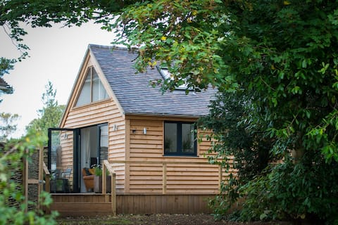 Brook Lodge was built and furnished to a really high specification in the grounds of the former village rectory. Lots of natural light inside. Large decking area, private garden and meadow to enjoy some of the best views in the Cotswolds.