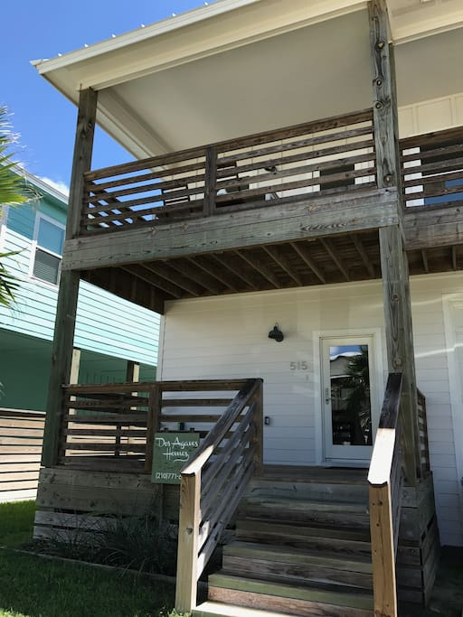 House facade with porch and upstairs balcony that overlooks birding sanctuary. Large outdoor dining table for al fresco dining!
