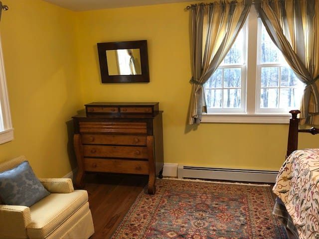 South Bedroom with dresser, upholstered chair and view to creek and horse pasture.