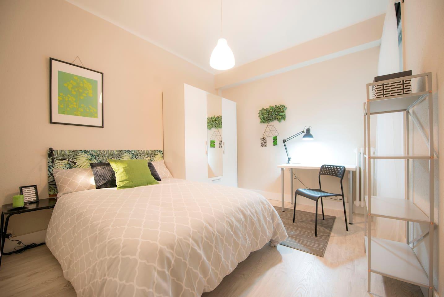 Habitación con cama doble, armario y zona de estudio