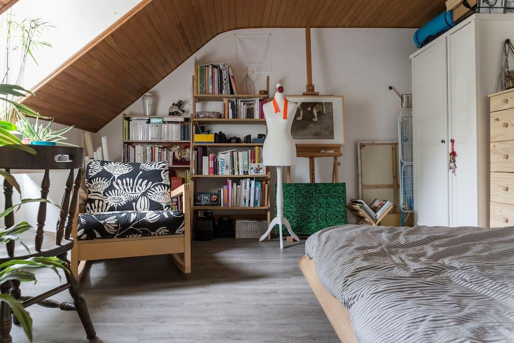 grande chambre avec lit, petit espace bureau, bibliothèque.