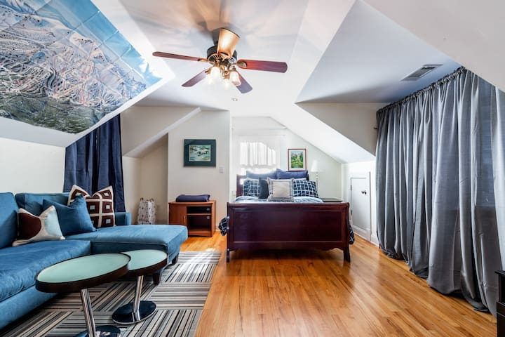 Up on the very top floor is a Queen bedroom! It is a very cool space with a small sectional sofa and a large ski poster on the wall.