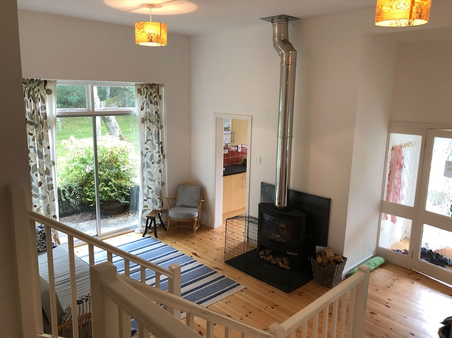 Downstairs sitting room with new woodburner.  View from upstairs landing showing the open plan sitting room through to dining area and access to kitchen.