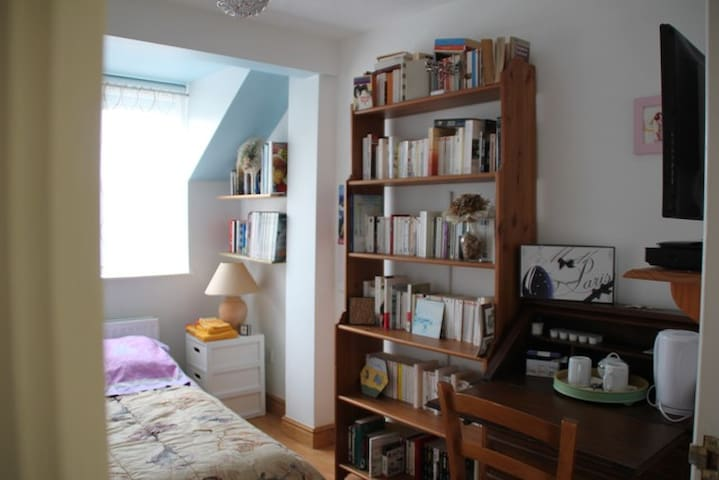 The bedroom with French, English books, a desk, a kettle, a TV and DVD player