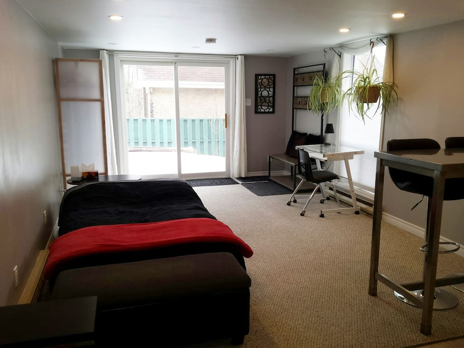 main area of guest suite with sofa configured as a bed, looking toward private back yard entrance