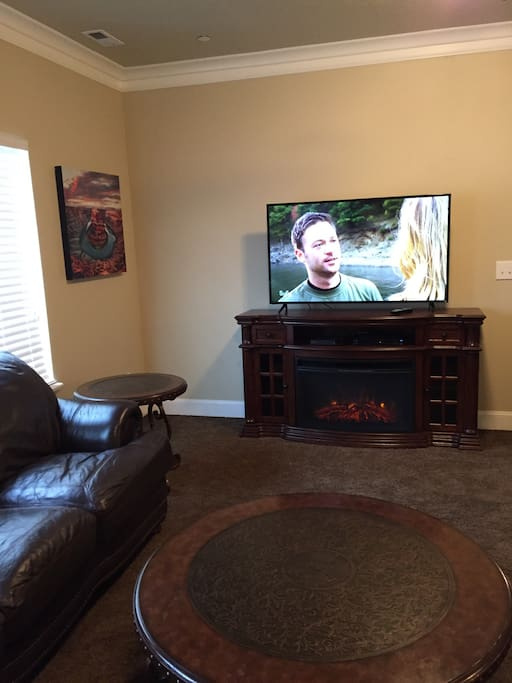 Living room with electric fireplace and large flat screen tv with Dish Network.