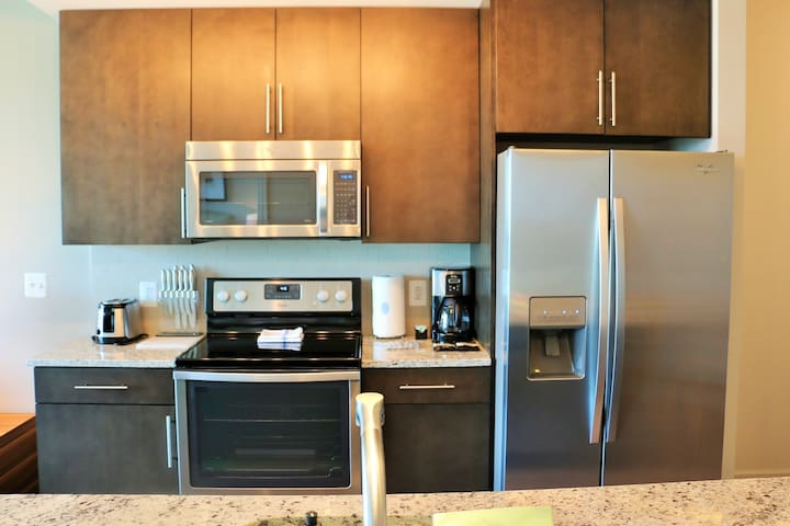 The deluxe kitchen features stainless steel appliances and dark wood cabinets