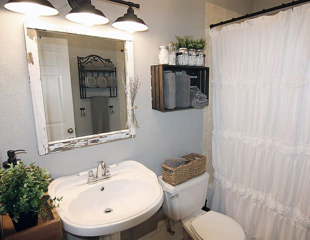 Prepare for your day in the farmhouse bathroom featuring locally handmade decor.