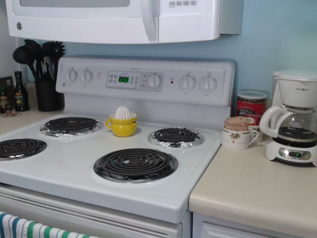 kitchen with stove, refrigerator, coffee pot, coffee, tea, sugar and cream