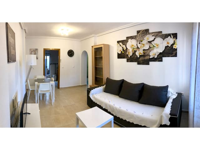 The living room with the new furnitures and the smart TV. The table is foldable for 6 guests and a sofa bed for two guests.