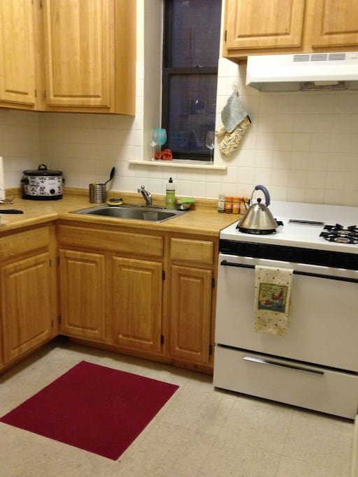 Full kitchen with gas stove and refrigerator.