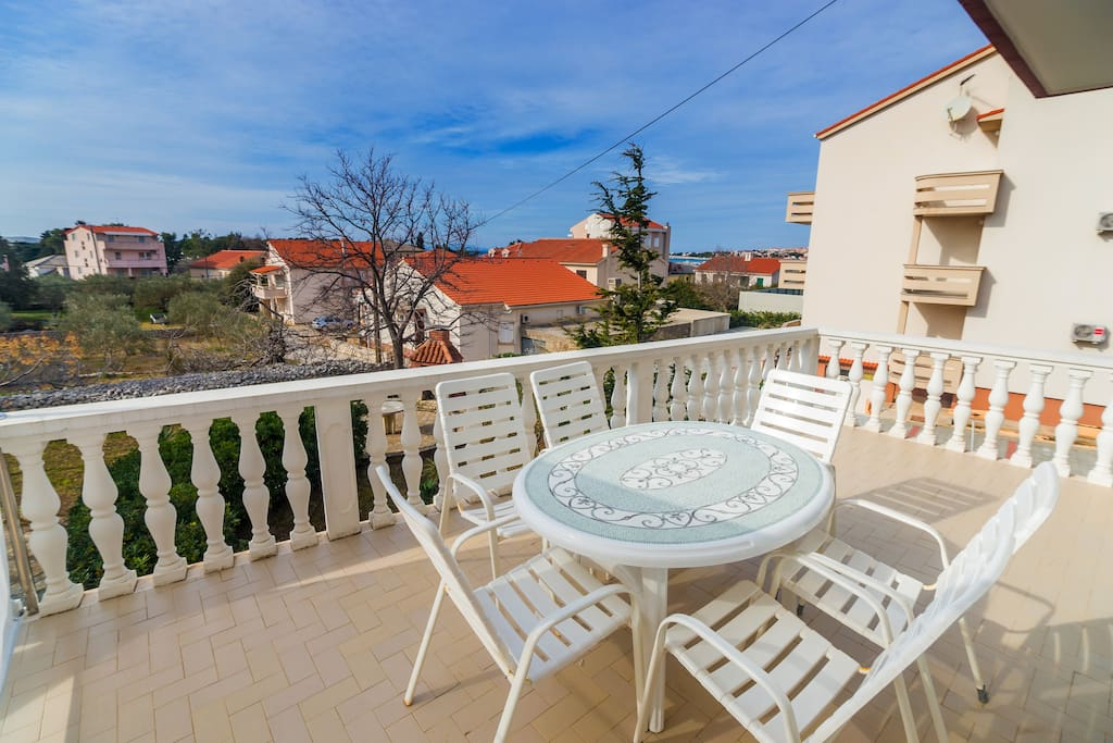 Apartment has a balcony with table and chairs