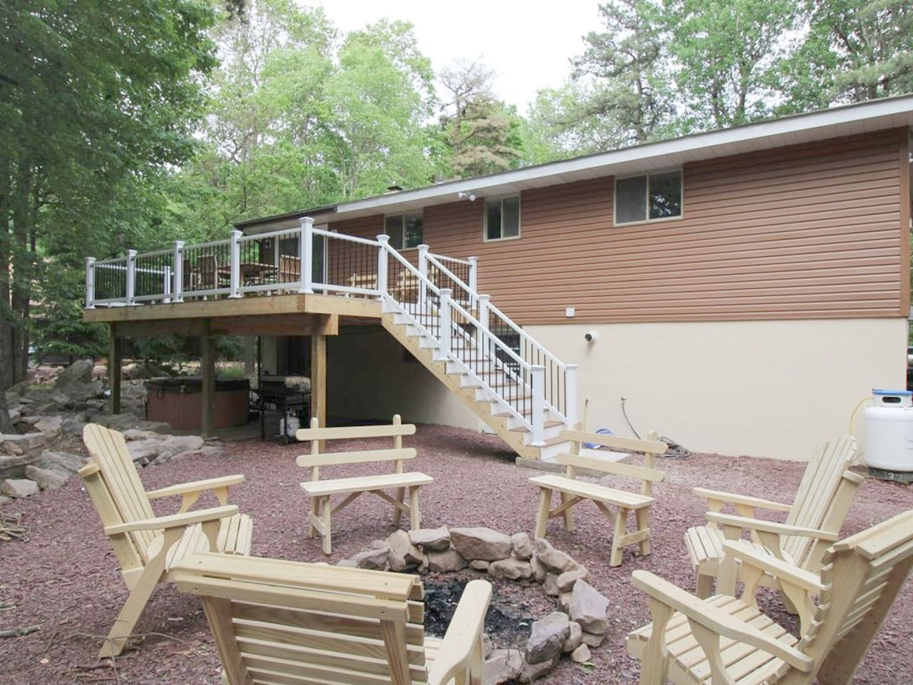 Back of house with fire pit and hot tub