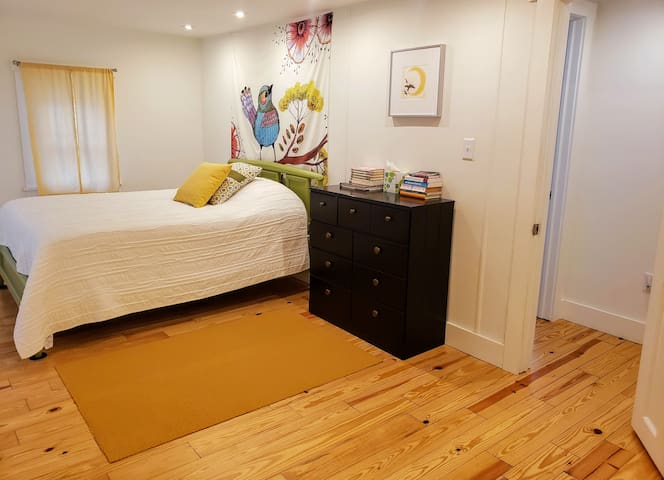 The front bedroom has a full size painted solid wood bed, custom drapes, and FLOR carpet over wood flooring.  And plenty of books!