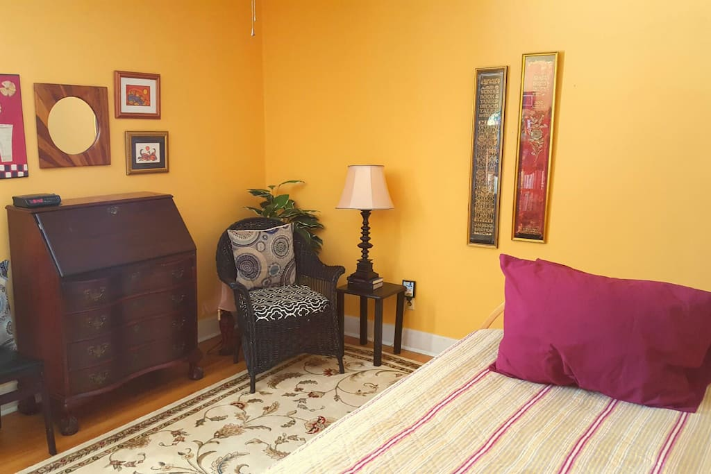 "one twin bed, desk, comfortable wicker chair  in ""reading corner."""